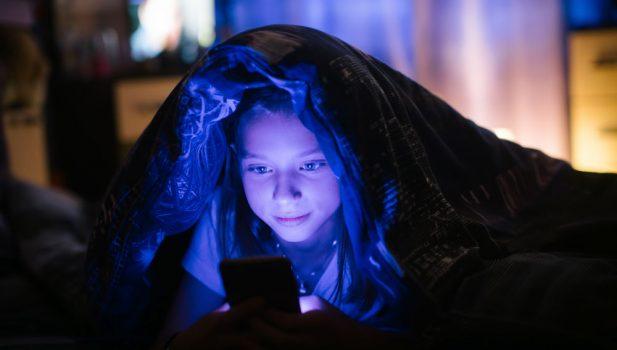 Niña usando tecnologia antes de dormir