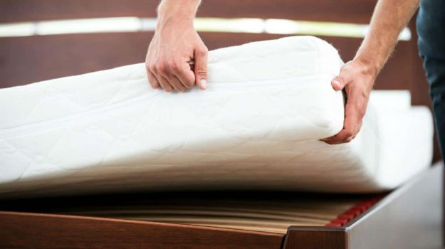 hombre girando un colchón